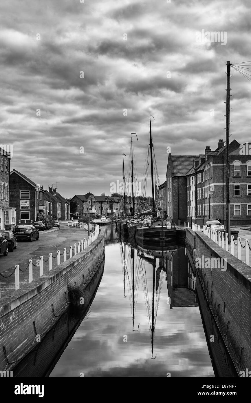 Old, vintage, barges anchored along the bank of the beck at Beverley with  houses and apartments in Beverley, Yorkshire. - Stock Image