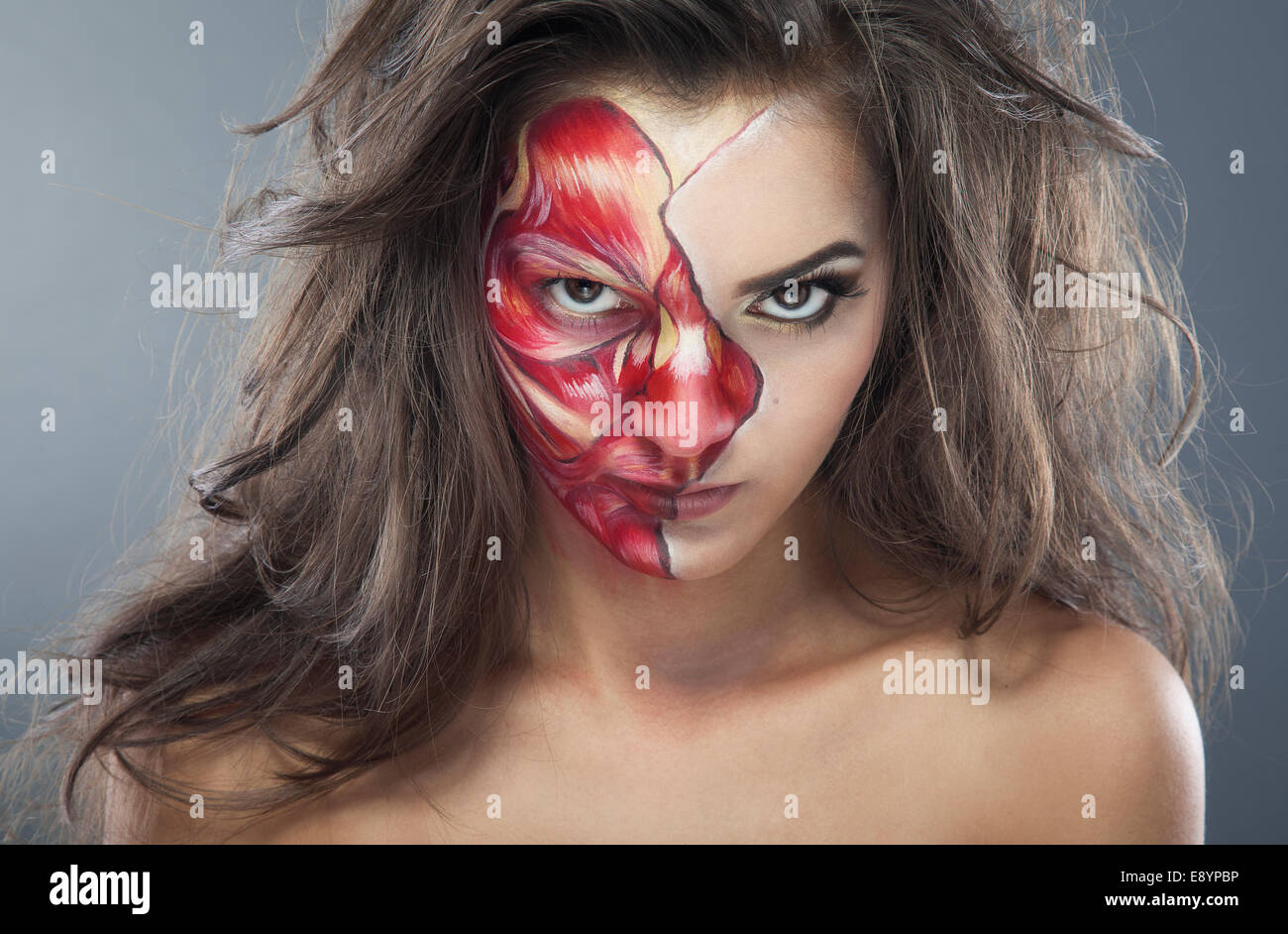 Girl zombie make-up for halloween holiday, half face beauty, another bloody - Stock Image