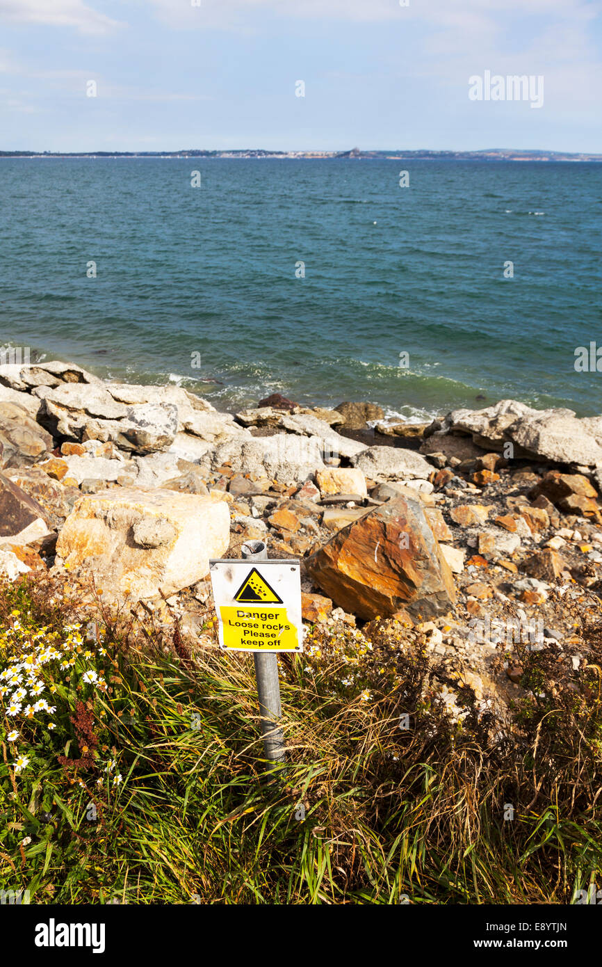 Danger loose rocks falling rock area sign on verge in Newlyn Cornwall UK England - Stock Image