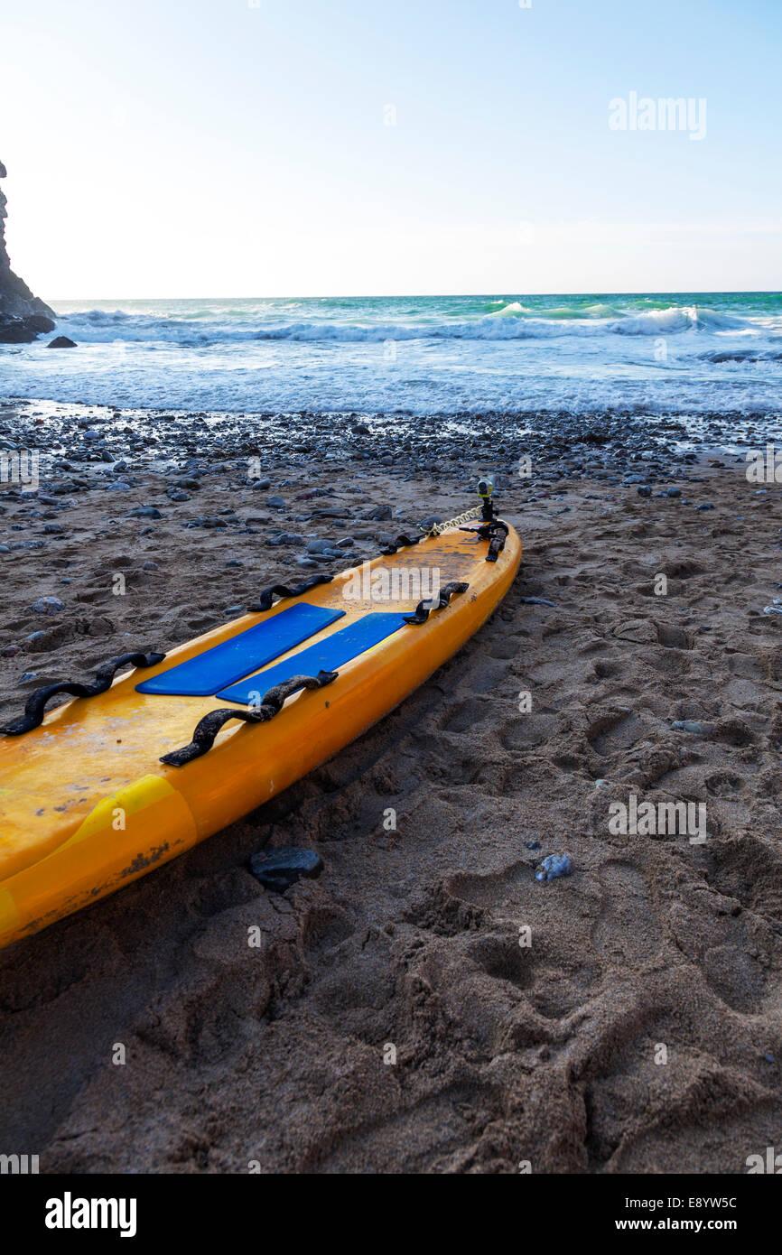 paddle board RNLI lifeguard life saving raft on beach in Cornwall UK England - Stock Image