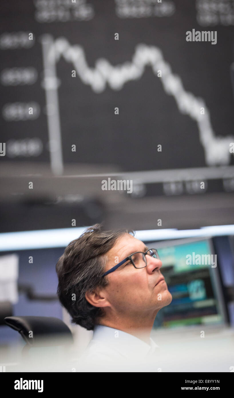 A stock trader sits in front of the DAX board on the trading floor of the stock exchange in Frankfurt/Main, Germany, - Stock Image