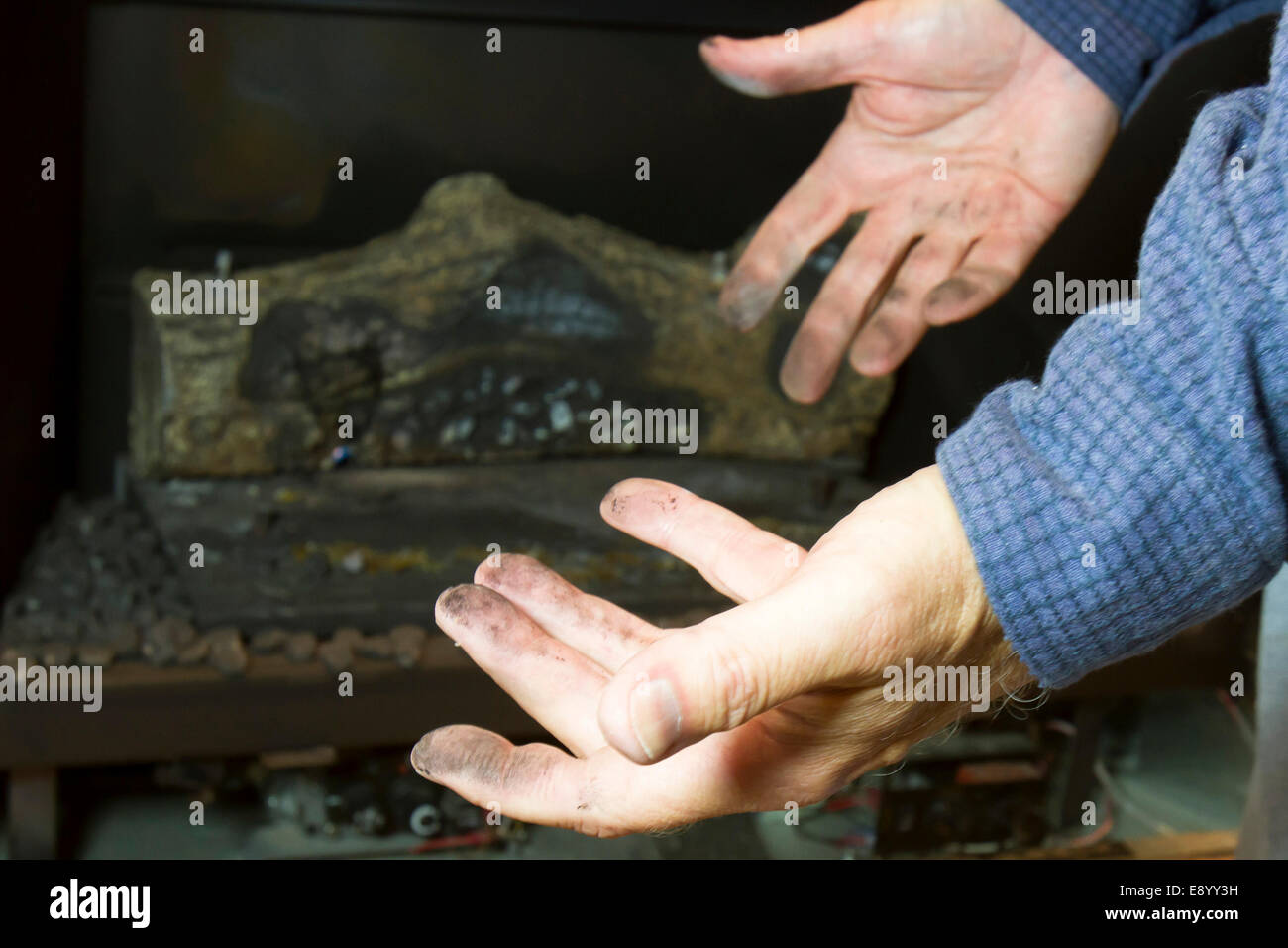 Diry man hands in front of gas fireplace - Stock Image