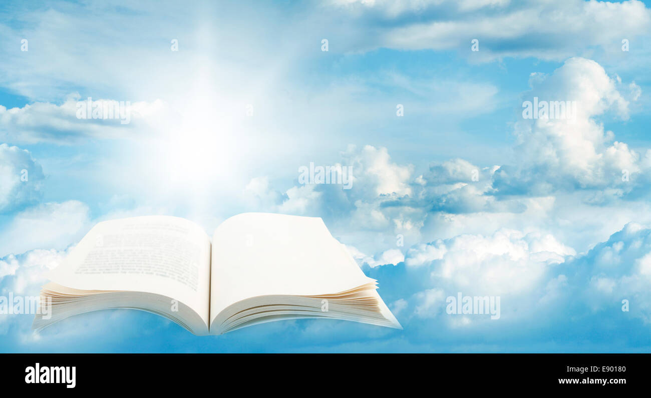 Open book in blue sky - Stock Image