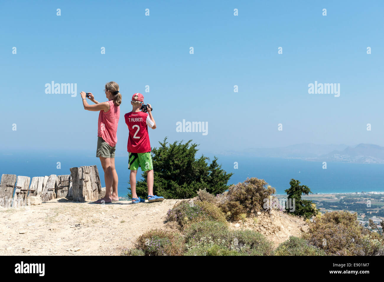 Mother and  son taking pictures from a vantage point in the mountains of Pyli, island of Kos, Greece - Stock Image