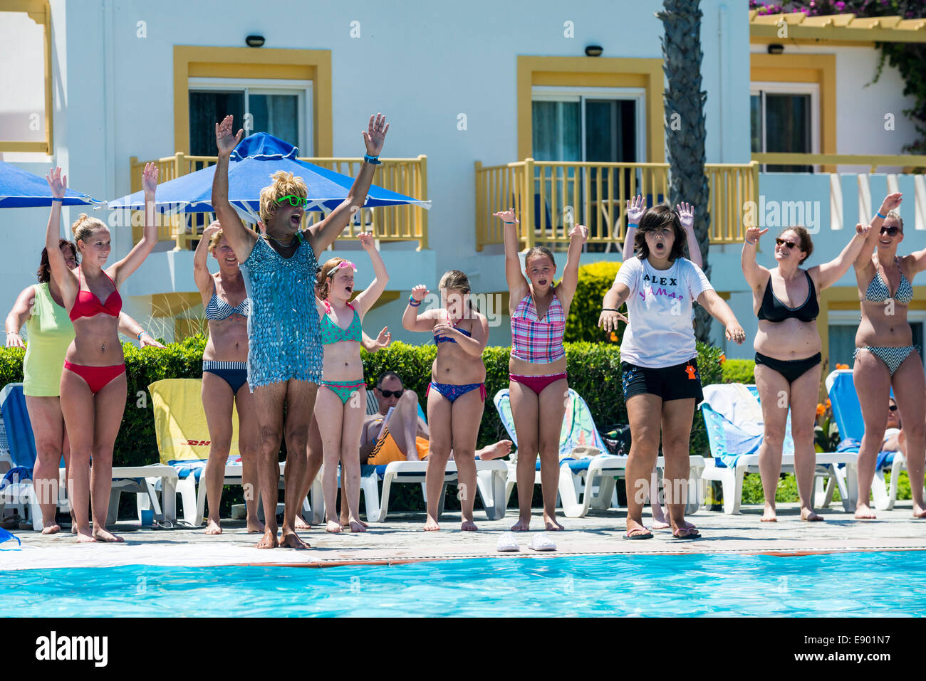 Holiday entertainer and hotel guests exercising a the swimming pool, Mastichari, Kos, Greece - Stock Image