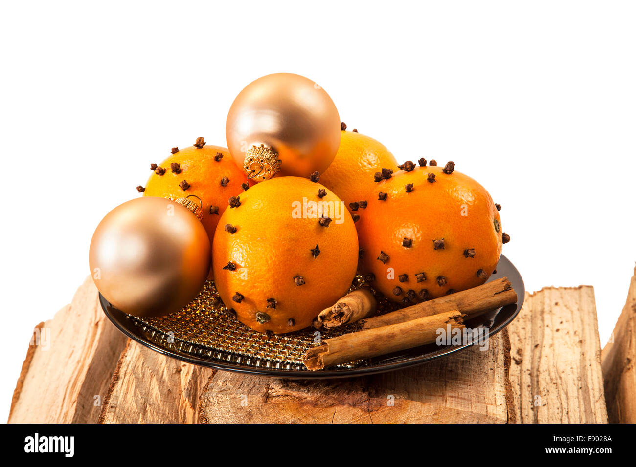 Christmas orange and baubles with cinnamon sticks on firewood over white background Stock Photo