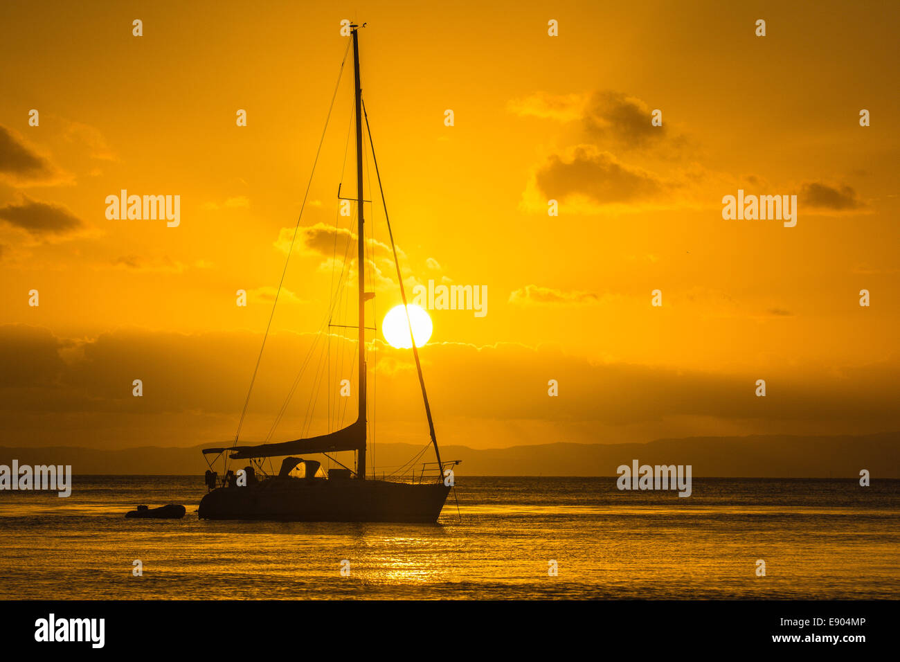 Boat anchored at sunset off of Tangalooma, Moreton Island, Queensland, Australia - Stock Image