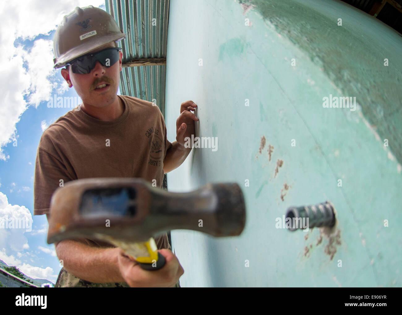 U.S. Navy Utilitiesman 2nd Class Robert Arthur, assigned to Construction Battalion Maintenance Unit 202, works on Stock Photo