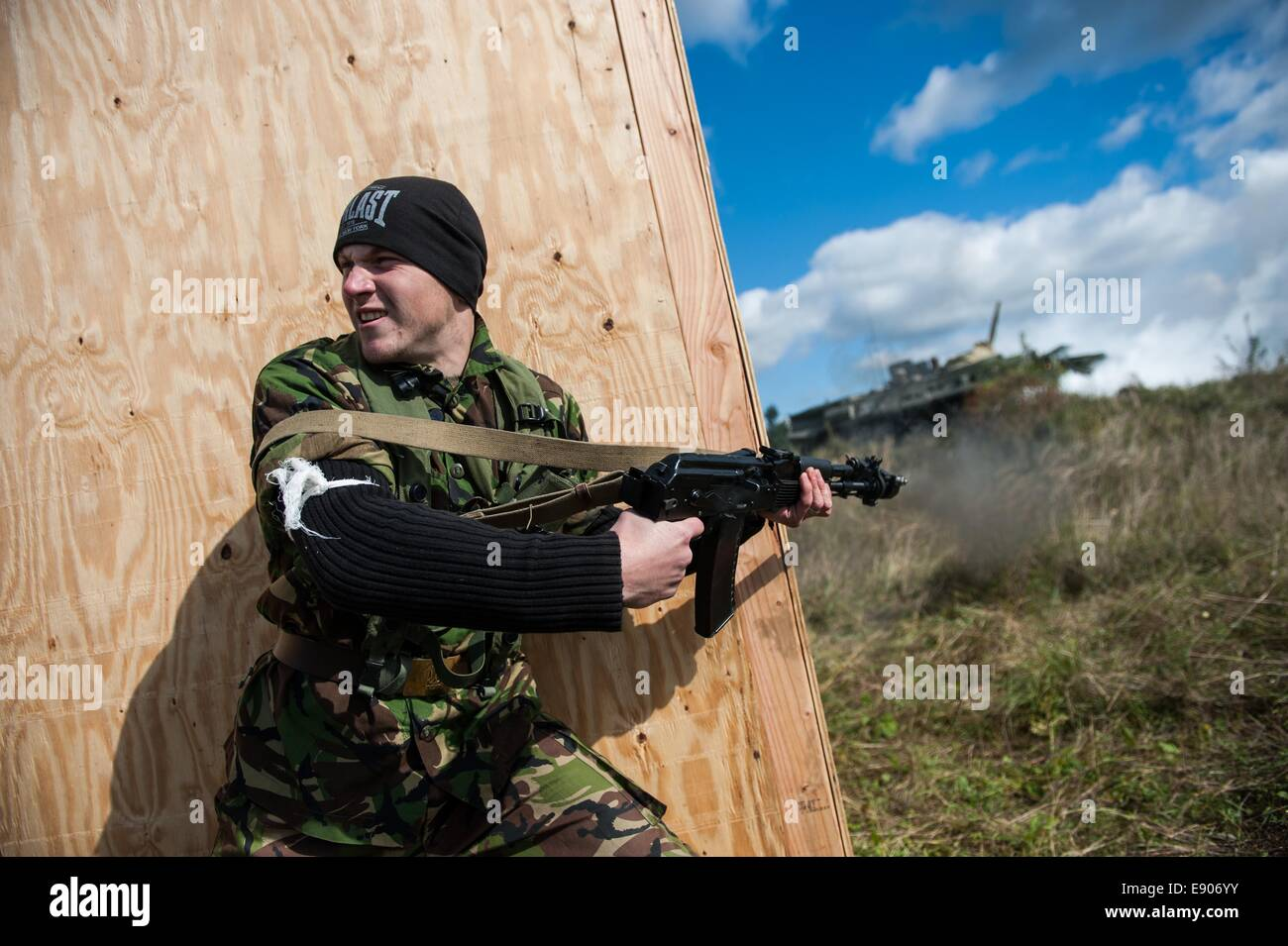 A Ukrainian military cadet acting as a simulated opposing force fires his rifle during a simulated high value target - Stock Image