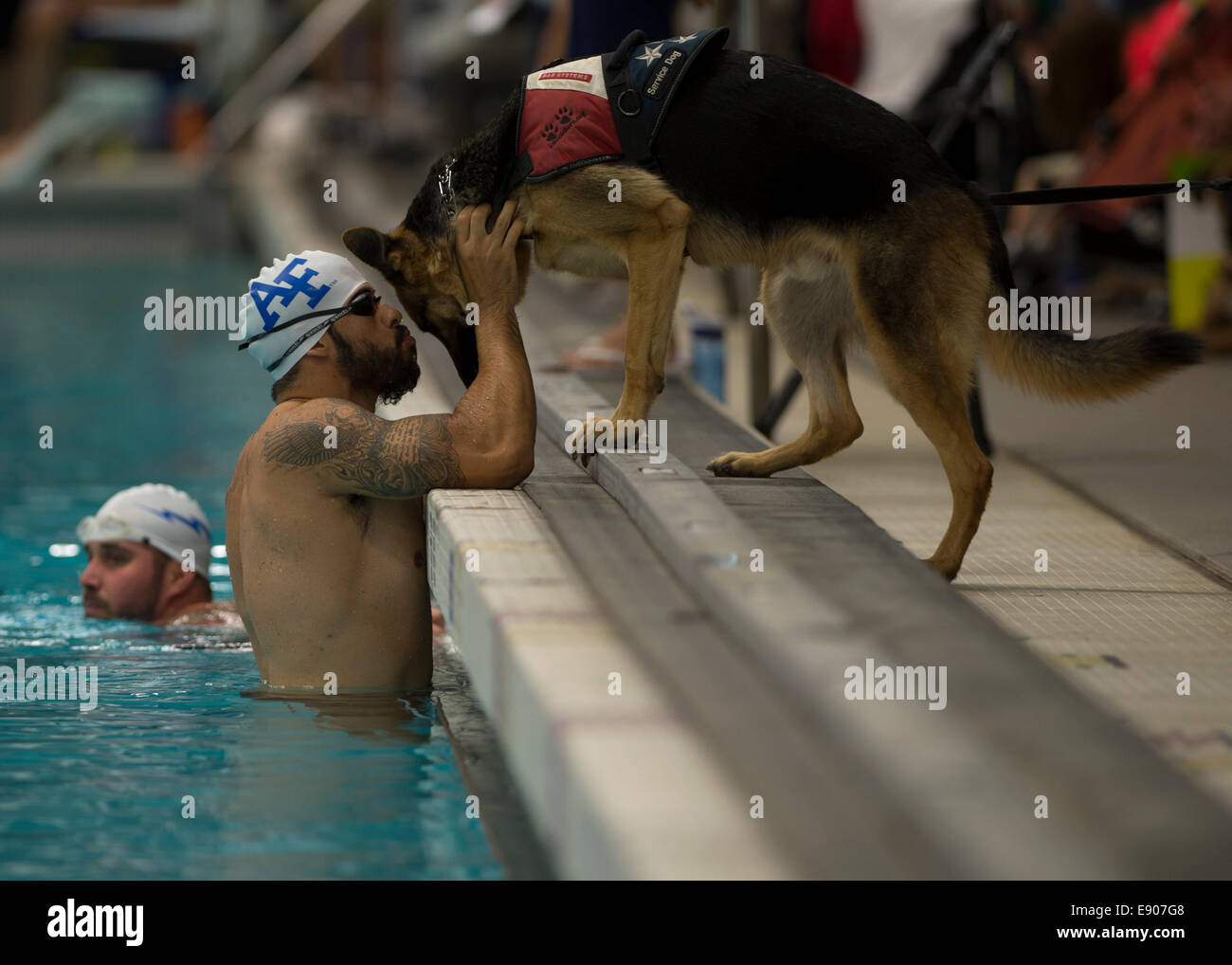 U.S. Air Force swimmer August O'Neill kisses his service dog, Kai, during the 2014 Warrior Games in Colorado Springs, Stock Photo