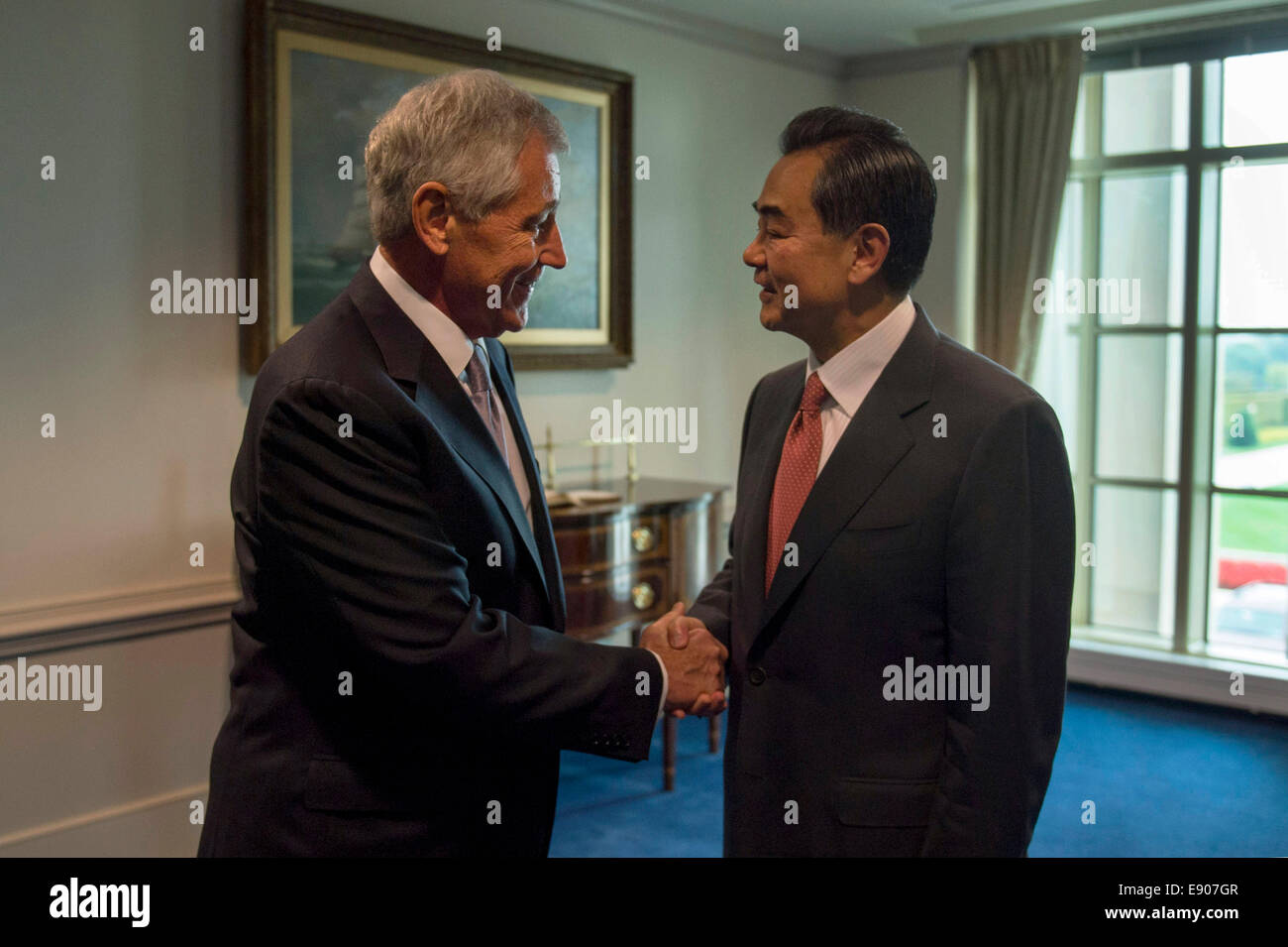 U.S. Secretary of Defense Chuck Hagel, left, welcomes Foreign Minister of the People's Republic of China Wang Yi Stock Photo