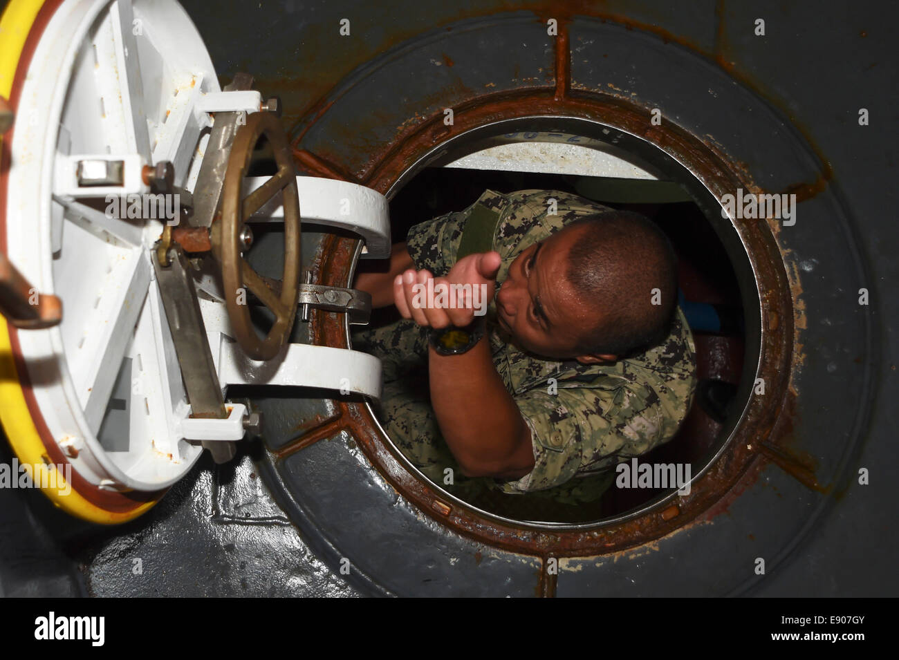 U.S. Navy Machinist's Mate 1st Class Ariel Ancheta climbs out of a hatch while conducting a tour of a U.S. Navy - Stock Image
