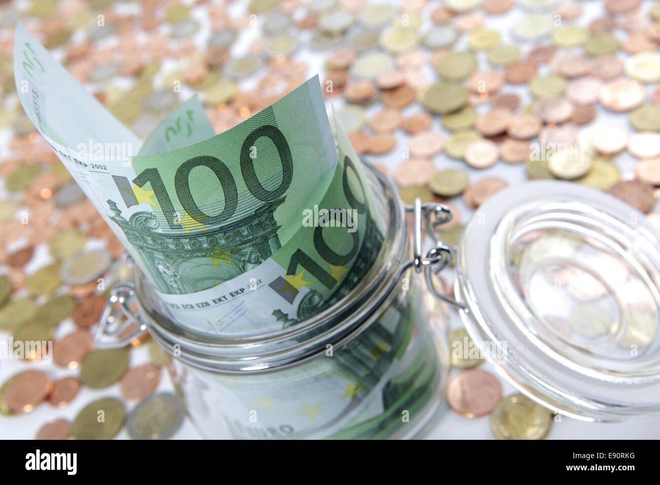 Glass jar with Euro bills and coins - Stock Image