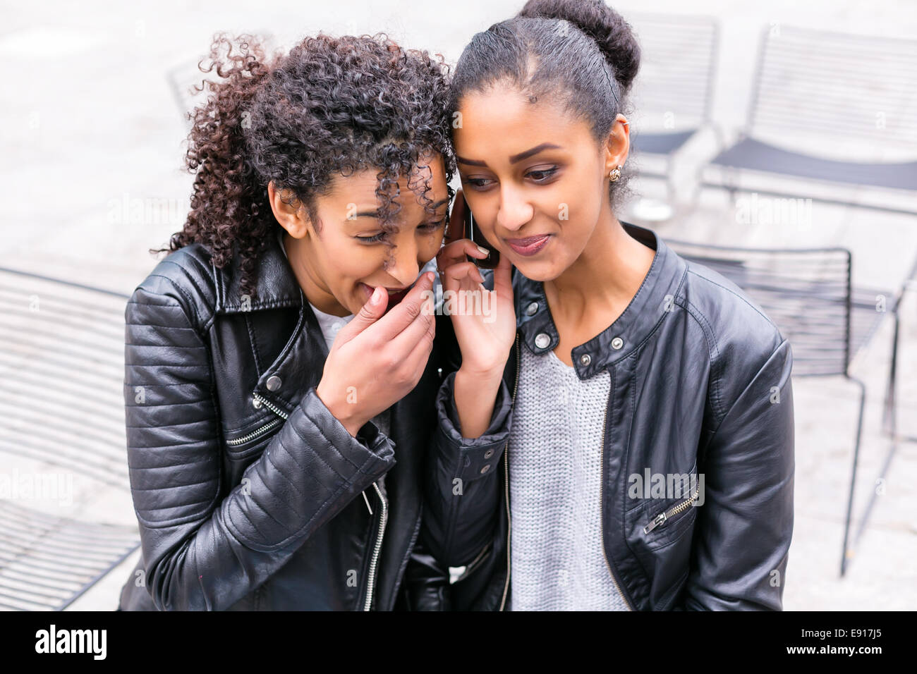 Two north African teen friends sitting together talking - Stock Image