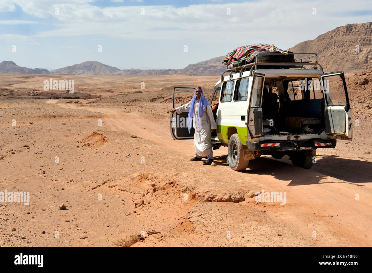 Bedouin Arab man with 4 wheel drive car on off road track in south Sinai desert, Egypt Stock Photo