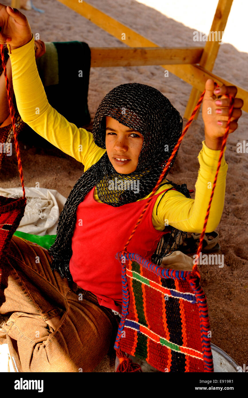 Young Bedouin Arab girl holding up hand crafted bag to sell at Bedouin camp in south Sinai desert - Stock Image