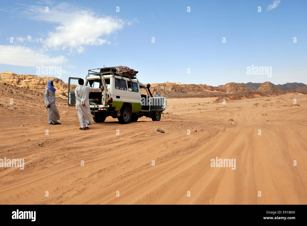 Twp Bedouin Arab men with 4 wheel drive car on off road track in south Sinai desert with doors open for cooling, Stock Photo