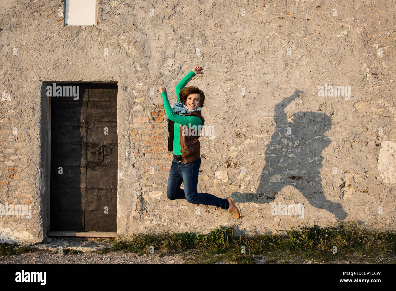 Young caucasian woman is jumping for joy in front of the old wall. - Stock Image