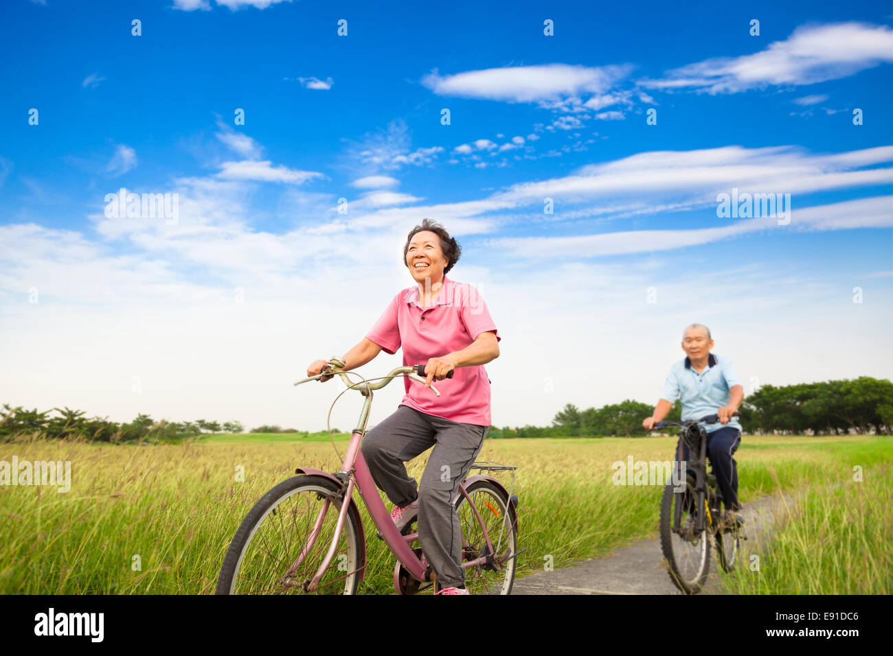 Happy Asian elderly seniors couple biking in farm with blue sky background - Stock Image