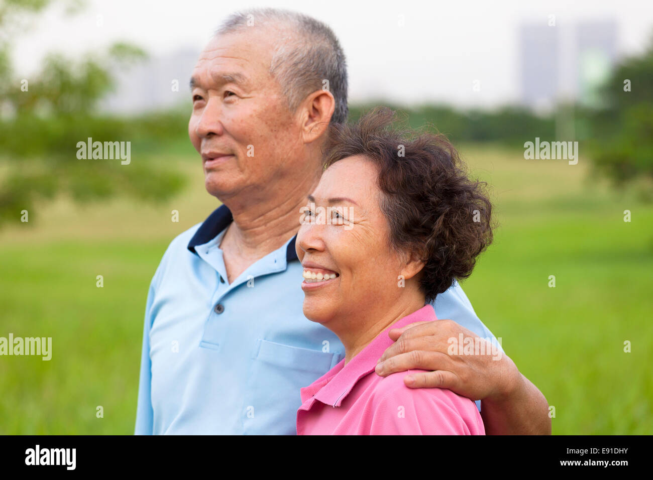 Happy elderly seniors couple in the park. retirement and health concept - Stock Image