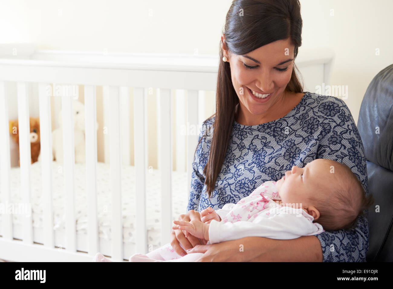 Happy Mother Sitting In Nursery With Baby - Stock Image