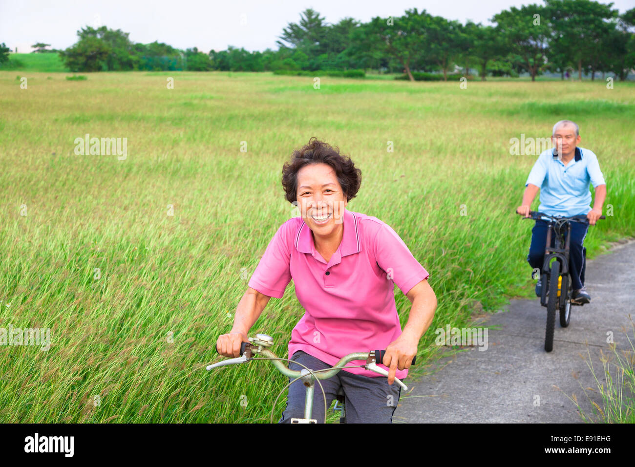 Happy asian seniors couple biking in the park.retirement and healthy lifestyle concept - Stock Image