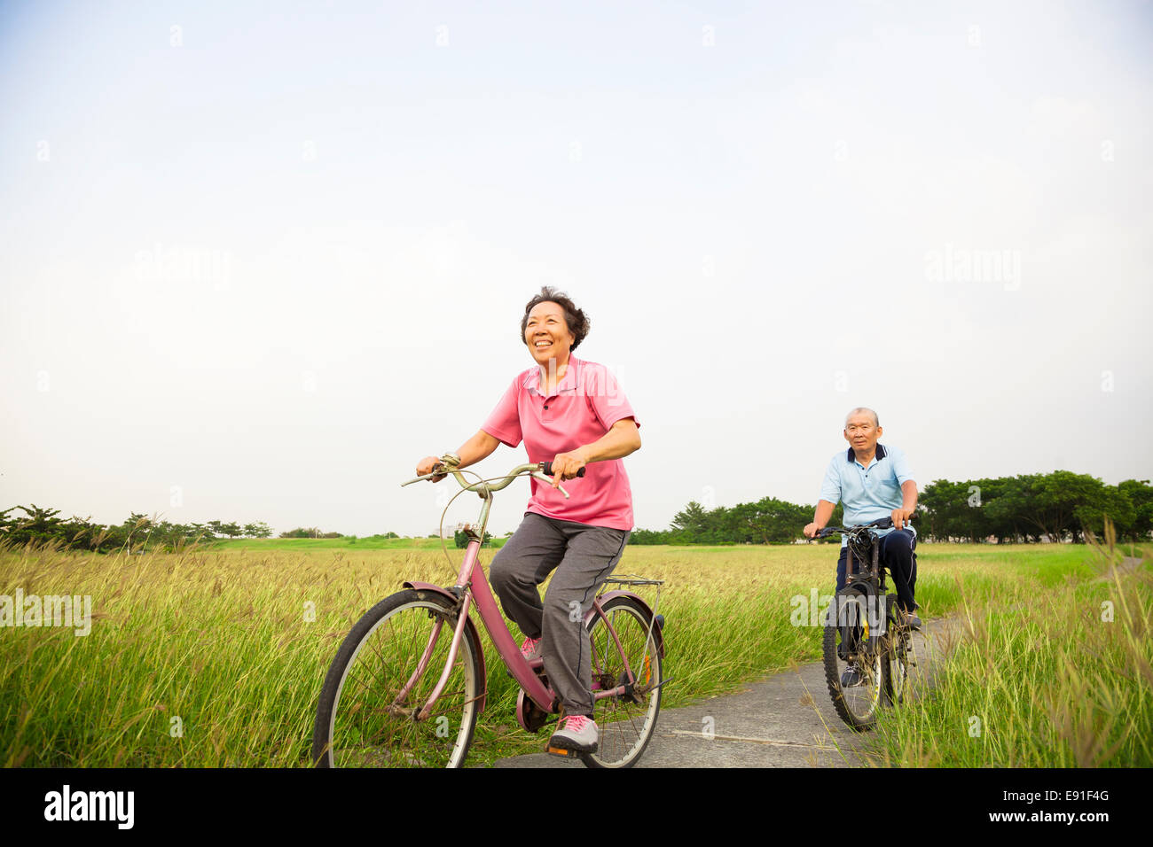 Happy Asian elderly seniors couple biking in the park - Stock Image