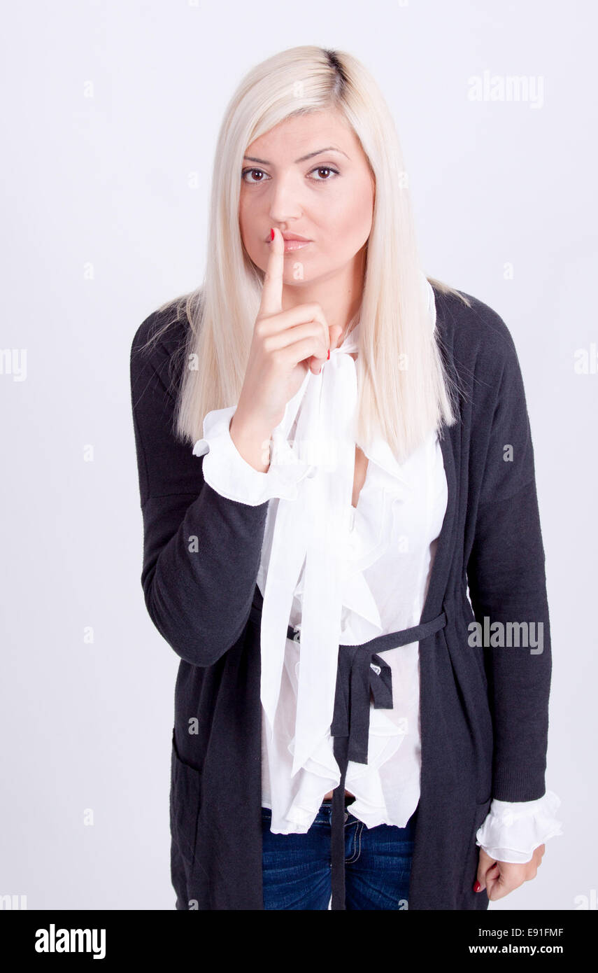 Young woman with finger on lips over white background - Stock Image