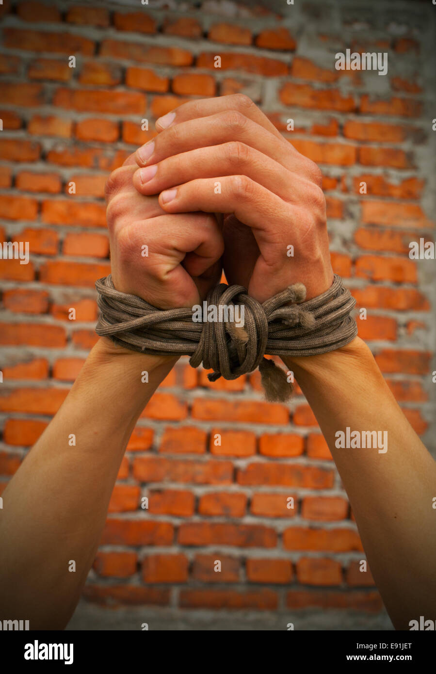 Hands tied up with rope against brick wall - Stock Image