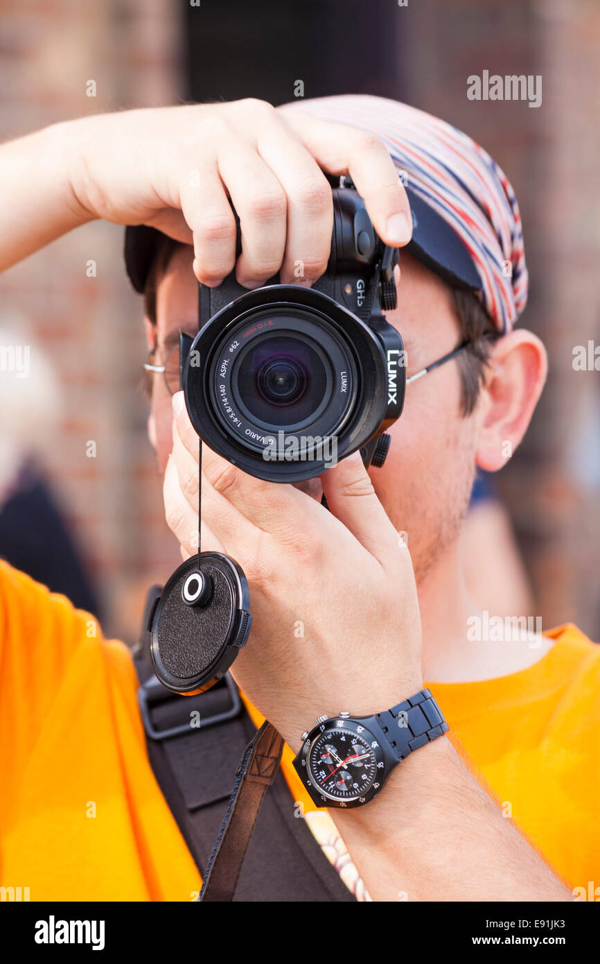 Photographer taking a photograph with a Lumix camera - Stock Image