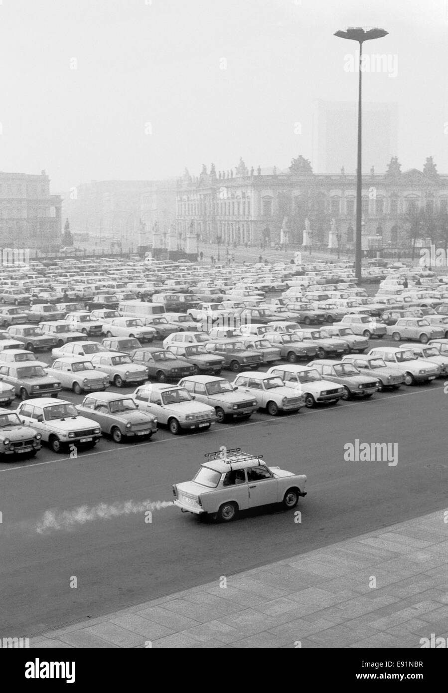 A smoky Trabant car driving along Museum Insel, off Unter den Linden in East Berlin around the time of re-unification - Stock Image