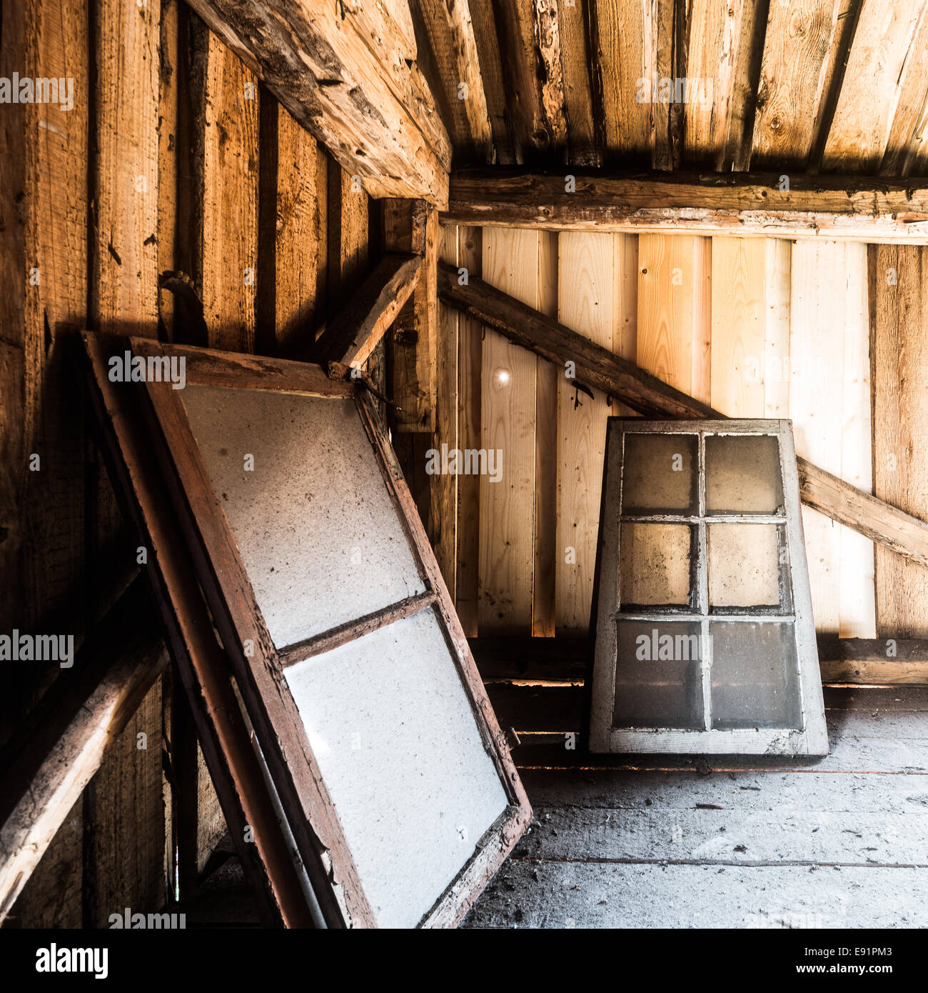 Dirty windows laying in a wooden barn - Stock Image