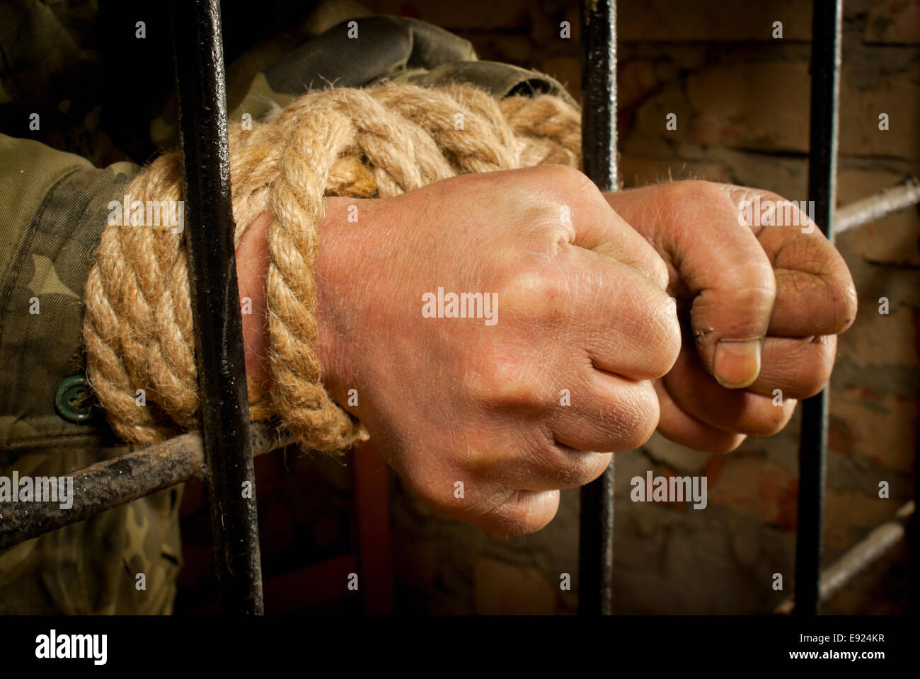 Hands of man tied up with rope - Stock Image