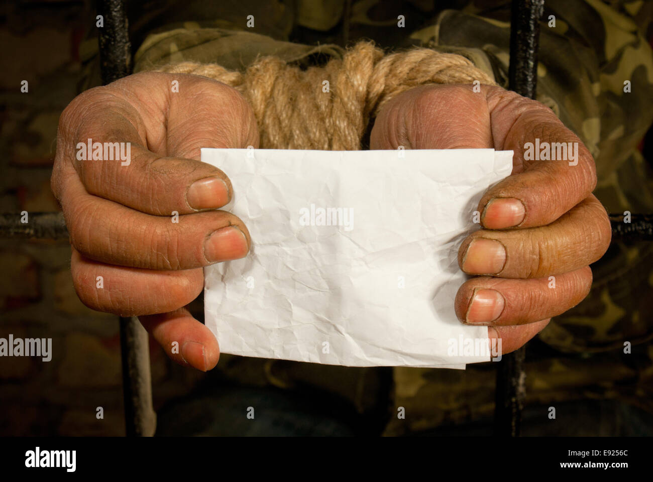 Man with hands tied up with rope - Stock Image