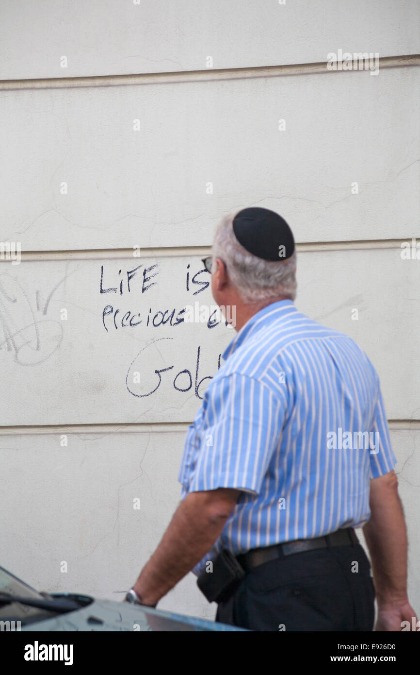 Jew walking past wall with Life is more precious than gold street graffiti written on in Old Town, Krakow, Poland - Stock Image