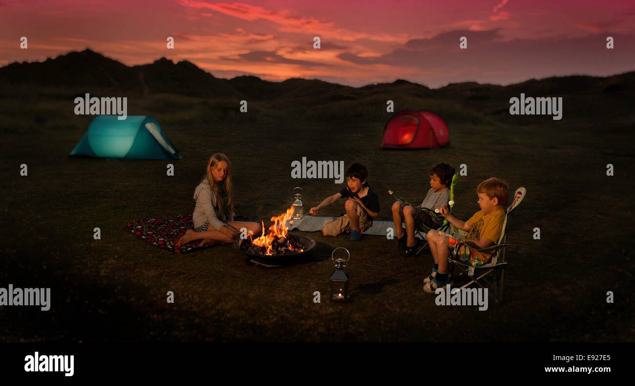 Children sitting around a campfire roasting marshmallows - Stock Image
