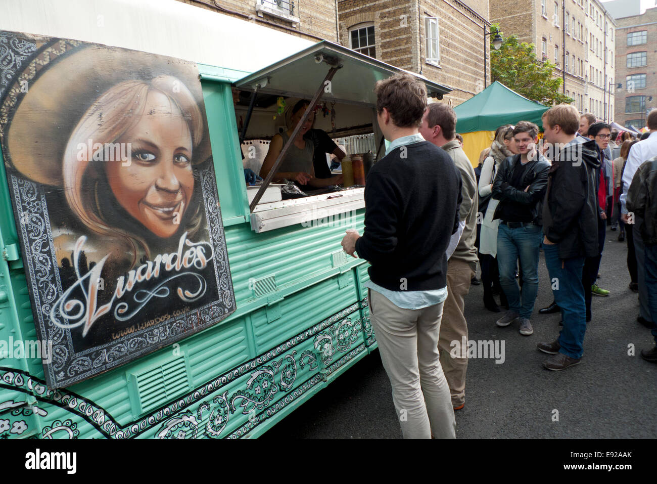 People queue at Whitecross Street Market near Old Street at lunchtime. Ethnic and artisan food stalls and vans supply - Stock Image