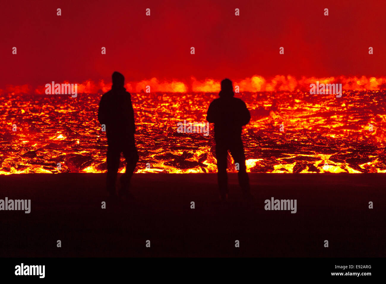 men in front of lava wall Stock Photo