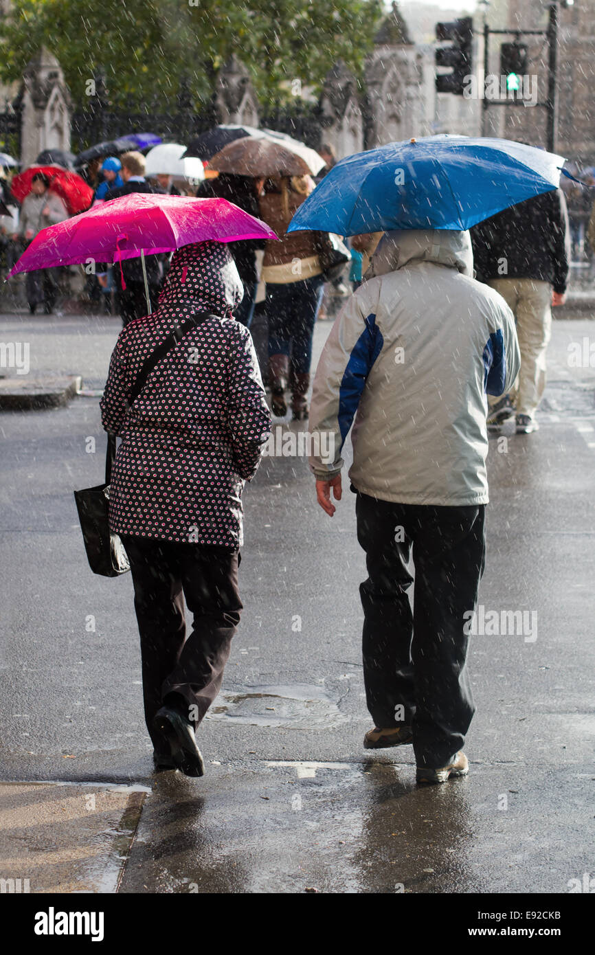 people crossing the street while it rains - Stock Image