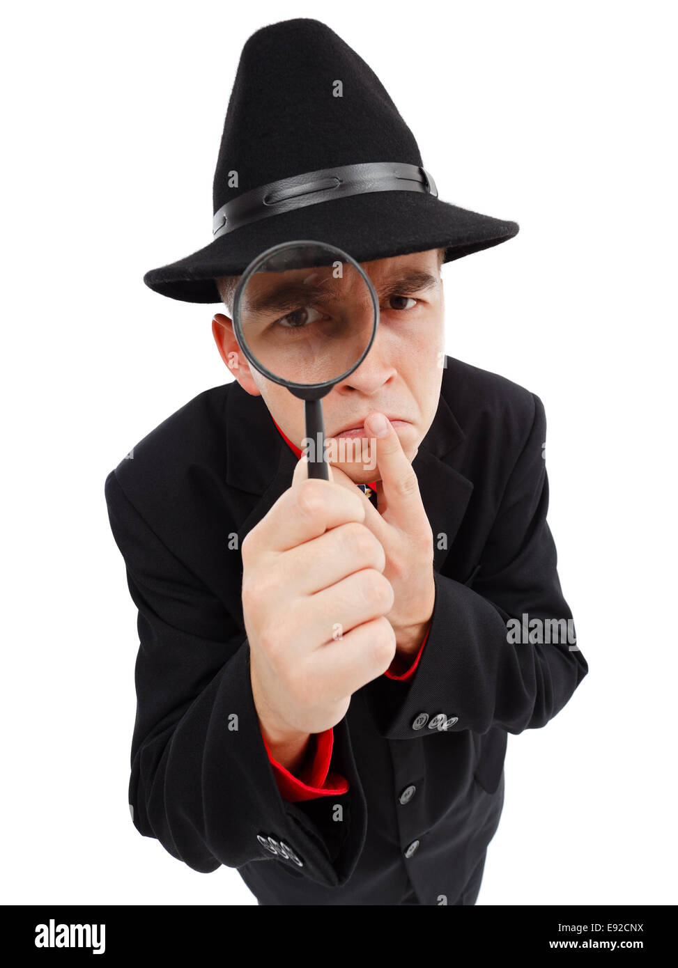 Detective with big hat, thumb on mouth, looking through magnifying glass seriously - Stock Image