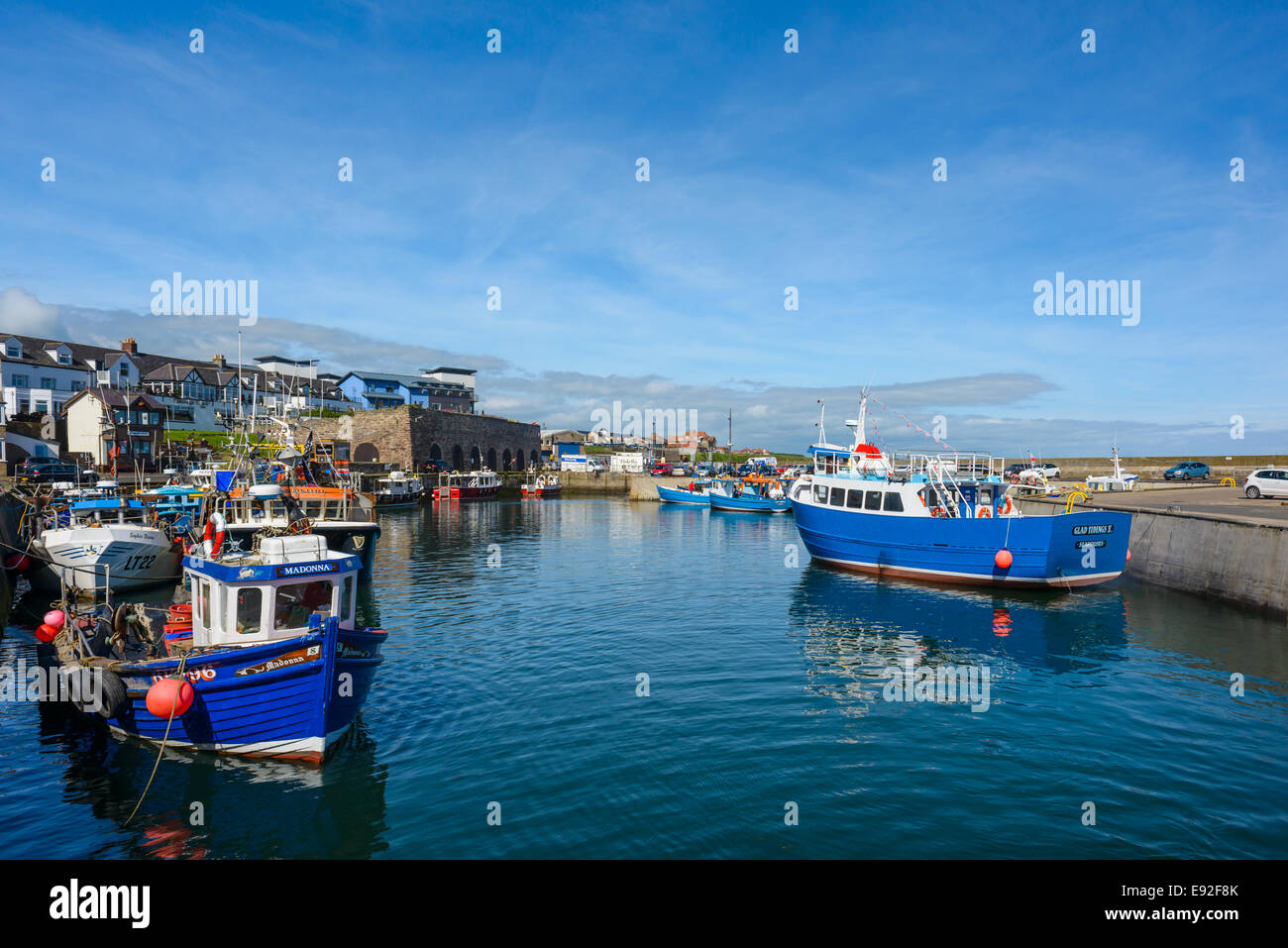 Seahouses Harbour Northumberland on a lovely clear day with a calm sea and boats moored to the piers jetties. - Stock Image