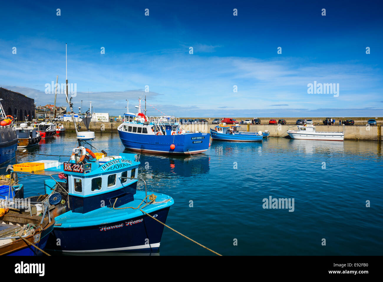 A boat is moved from its harbour mooring to take day trippers out to sea on a wildlife cruise, Seahouses, Northumberland, - Stock Image