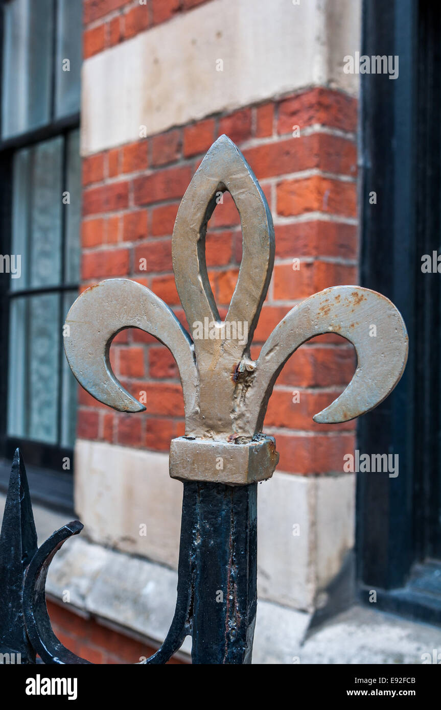 A bronze colored fleur di lis fence post top is isolated against a red brick wall. - Stock Image