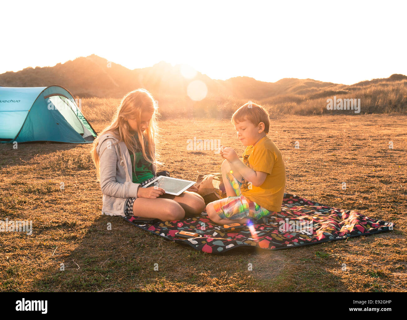 Children camping on picnic blanket with ipad in summer. Brother and sister camp holiday in UK England sand dunes - Stock Image