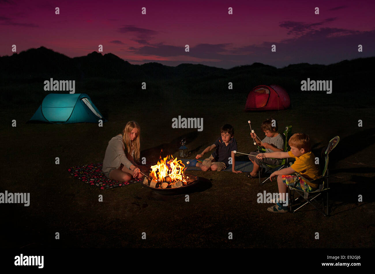 Children sitting around a campfire roasting marshmallows - Stock Image