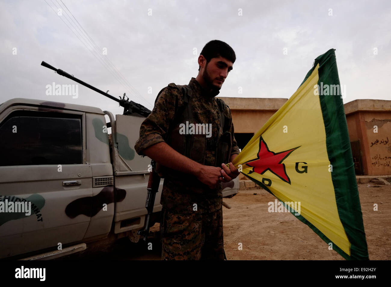 A Kurdish fighter folds the official flag of the Kurdish People's Protection Units YPG in a military base in Al Stock Photo