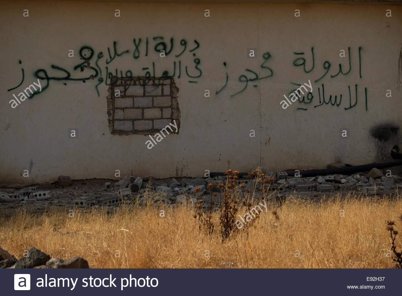 A writing in Arabic in a wall reads The Islamic State in the