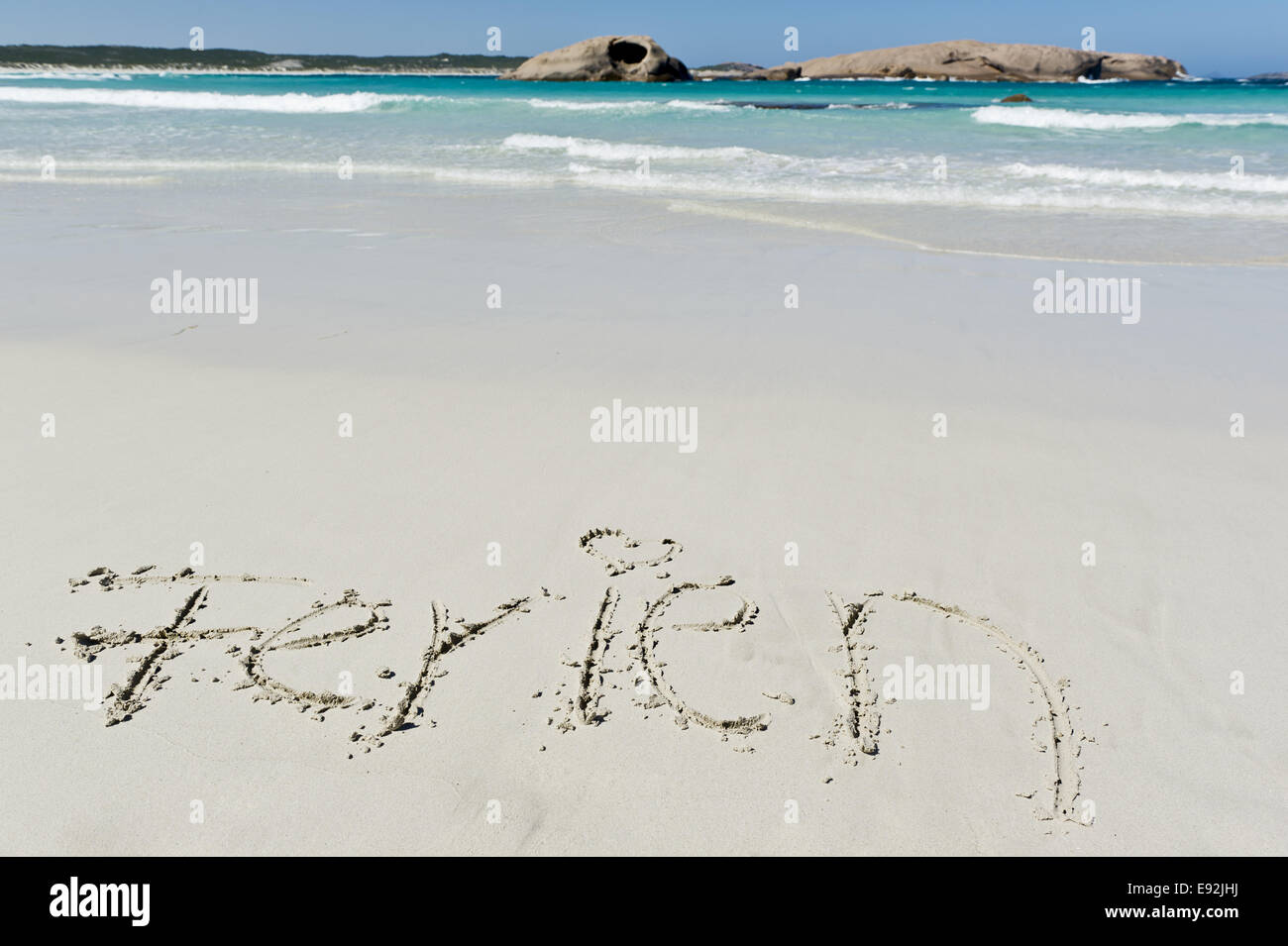 Holiday written in the sand - Stock Image