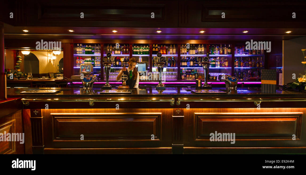 Woman pulling pint in hotel bar - Stock Image