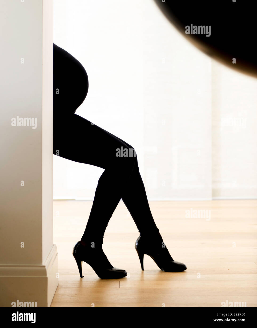 Pregnant woman in high heels - Stock Image